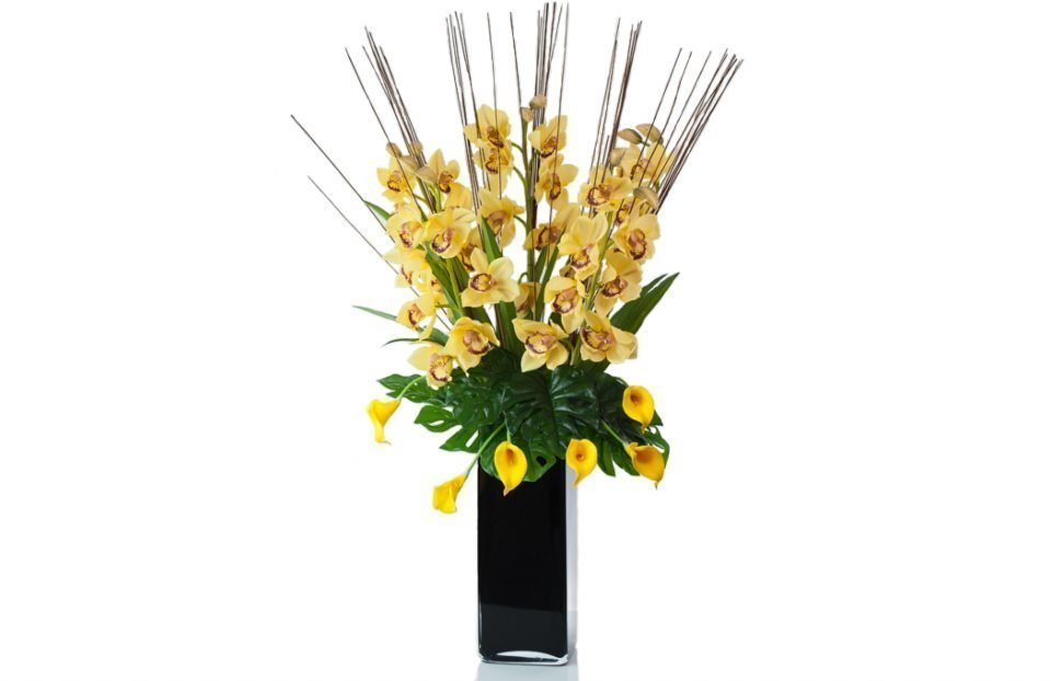 Artificial yellow cymbidium orchids in black tank vase front facing