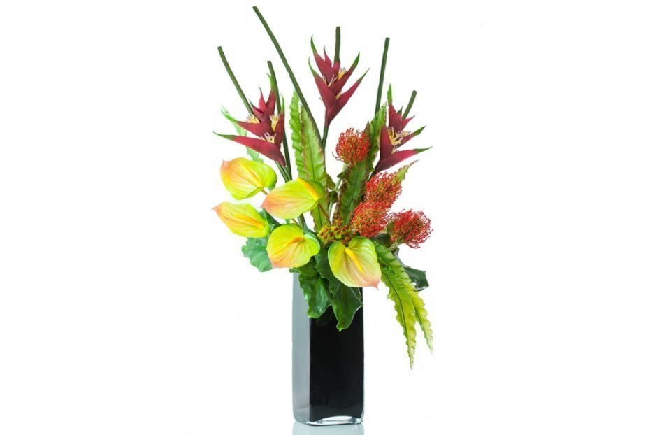 Tropical heliconias, anthuriums, nutans spray orange, orange hypericum in black tank vase, front facing
