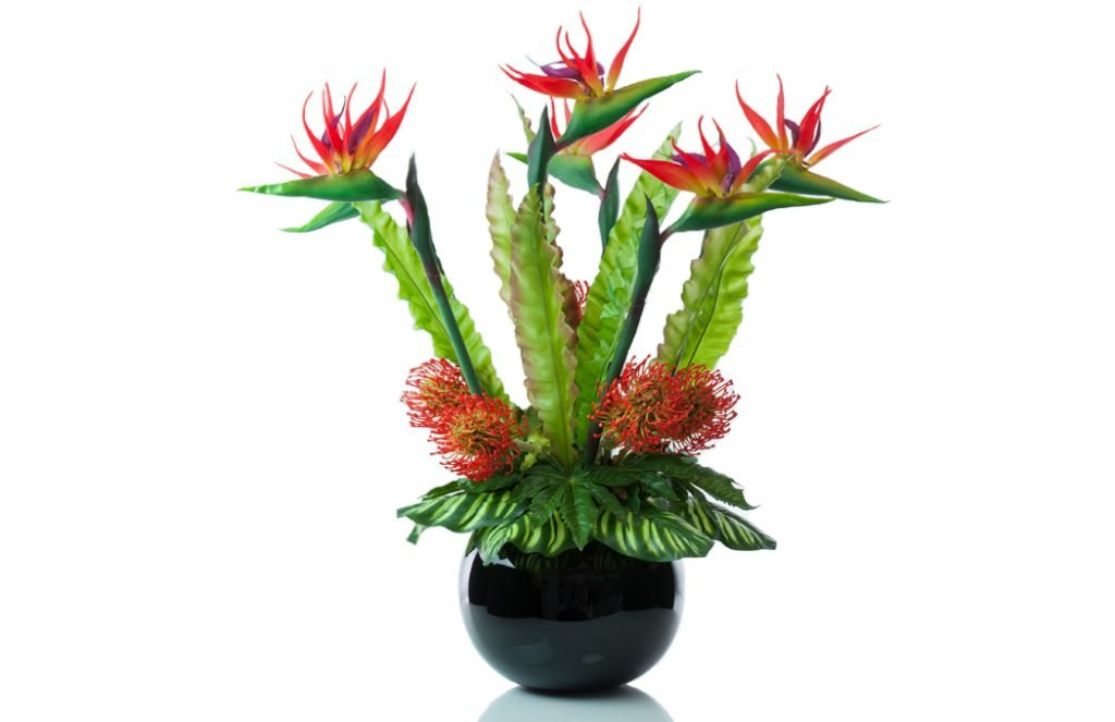 Faux strelitzias (birds of paradise), nutans spray orange in a black fishbowl.