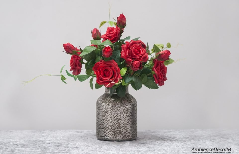 Red lifelike roses in vase