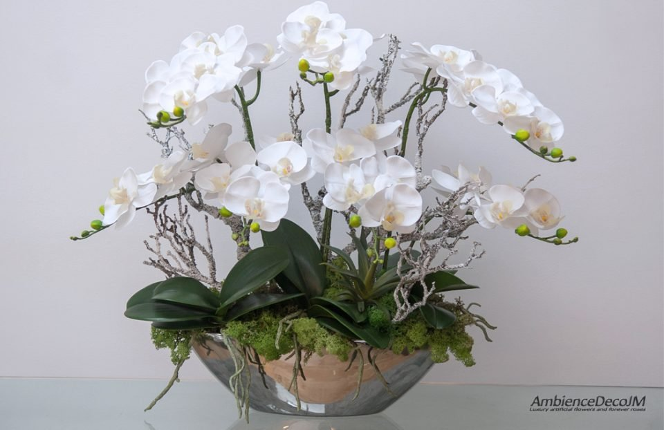 Lifelike orchids in a mirrored boat vase