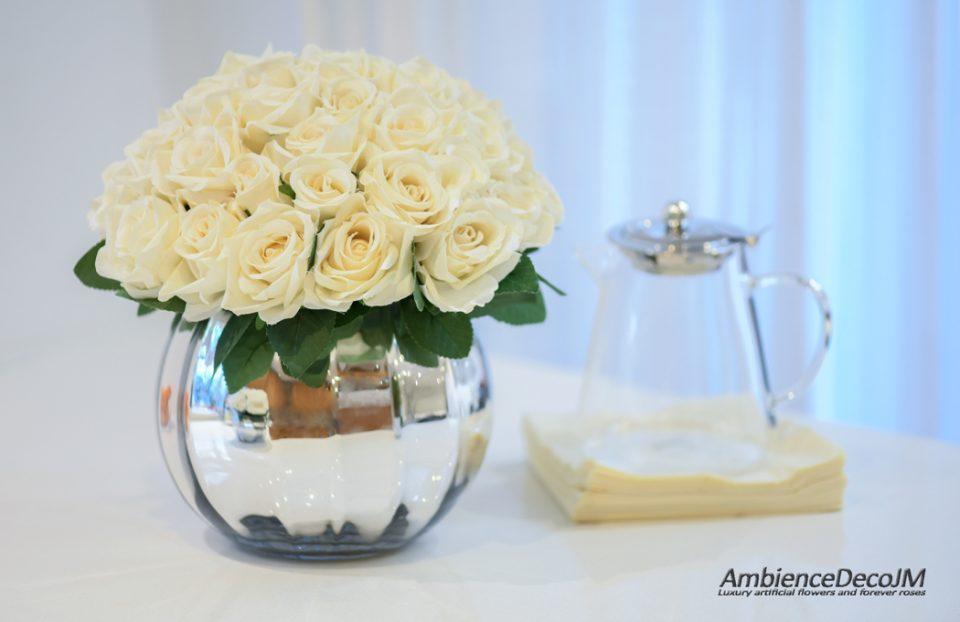 Silk roses in fishbowl vase